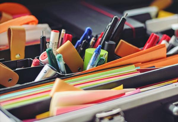 imagem com vários papeis e canetas, no ambiente de trabalho