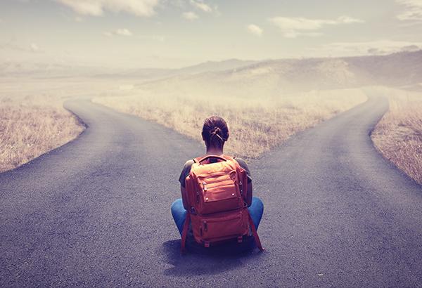 Pessoa sentada entre duas estradas